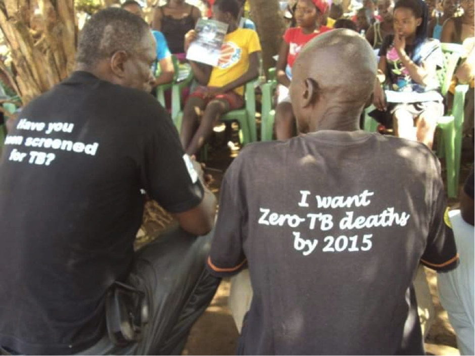 Two people with their backs to the camera, both wearing t-shirts that read 'I want zero TB death by 2015'
