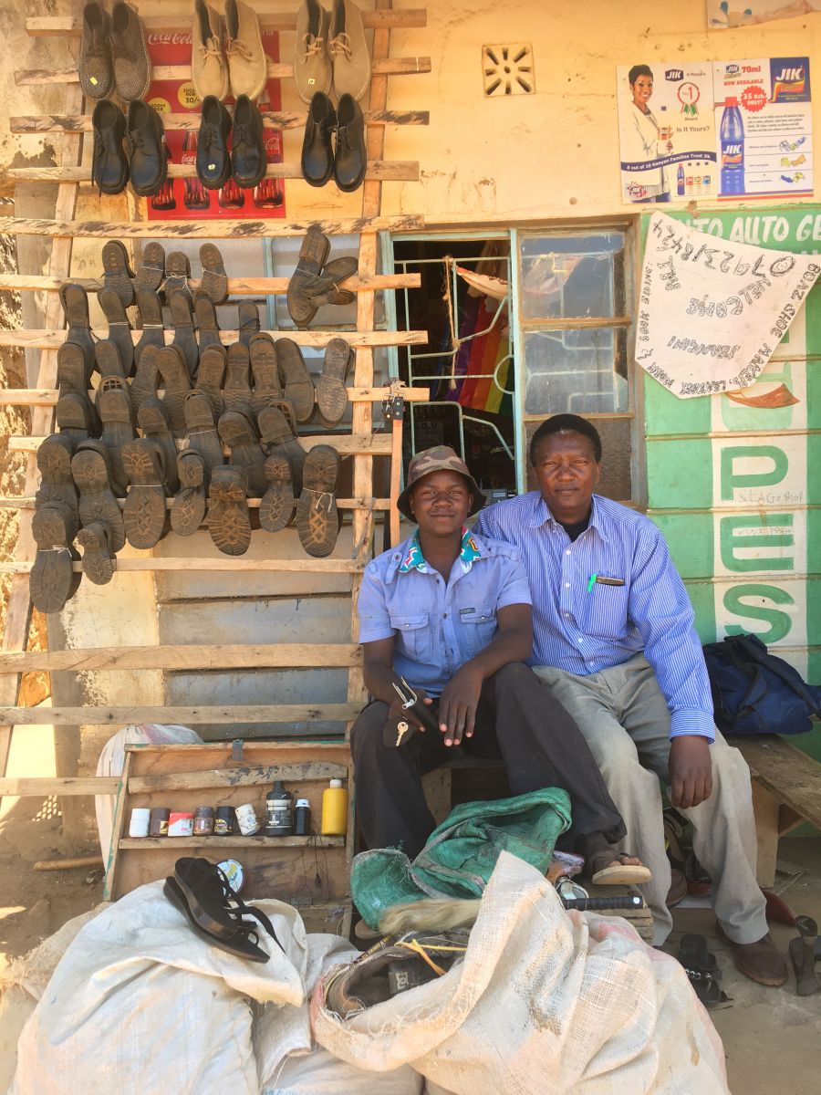 22 year old cobbler Boars (left) sits with his community health worker Stanislaus outside his shop.