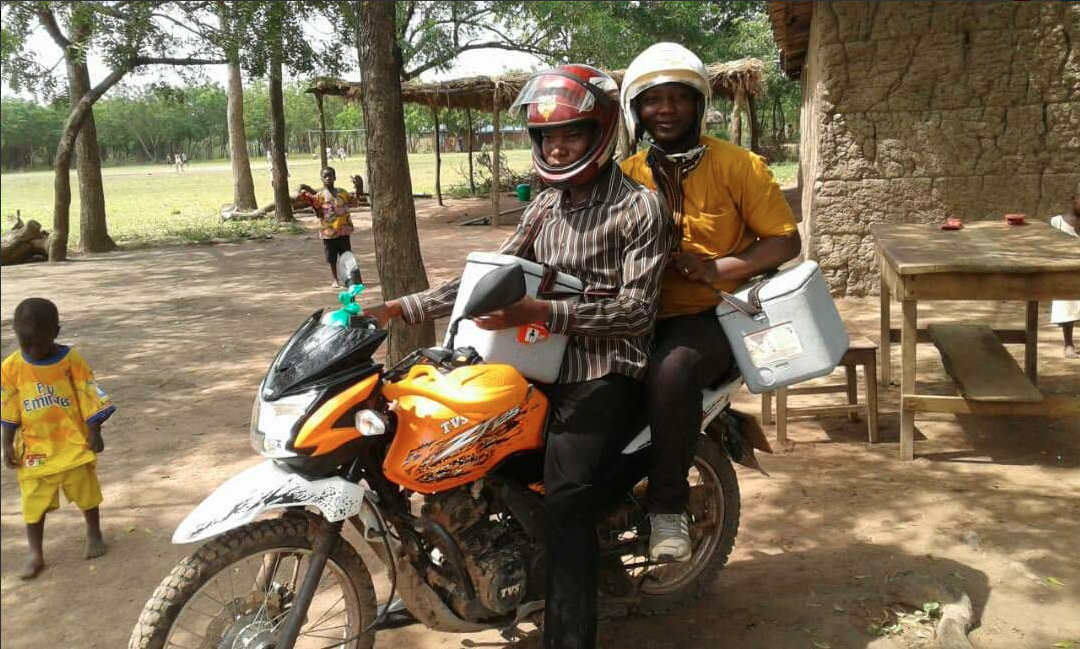 Edmund hopping on a bike to provide immunisation services in hard to reach island communities in Afram Plains, Ghana.