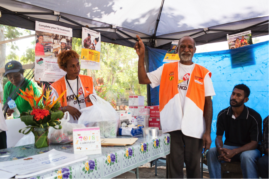 Volunteer health worker Rodney Kove speaks to people with TB about the side effects of their treatment at an outreach post outside his home in ATS settlement, Port Moresby